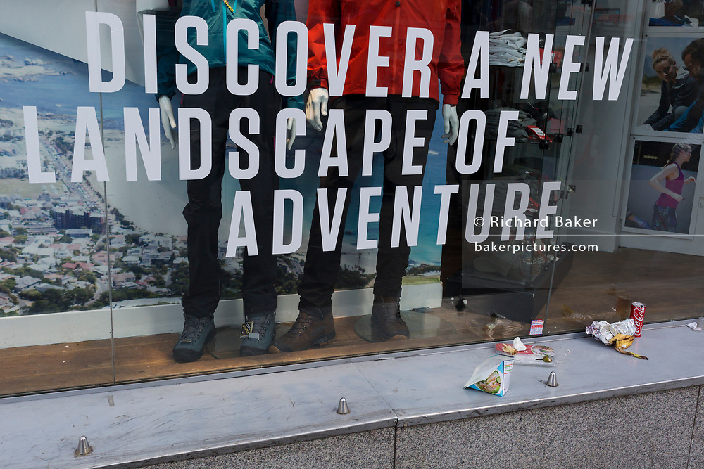 Abandoned litter outside an outdoors and adventure shop and its message to discover new landscapes, on 10th May 2017, in the City of London, England.