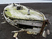 On Deception Island, an old wooden boat decays on a black sand beach. In the South Shetland Islands near the Antarctic Peninsula, Deception Island has one of the safest harbors in Antarctica. Deception Island is the caldera of an active volcano, which caused serious damage to local scientific stations in 1967 and 1969. The island is now a tourist destination and scientific outpost, with research bases run by Argentina and Spain. The island is administered under the Antarctic Treaty System. The sea surrounding Deception Island is closed by ice from early April to early December.