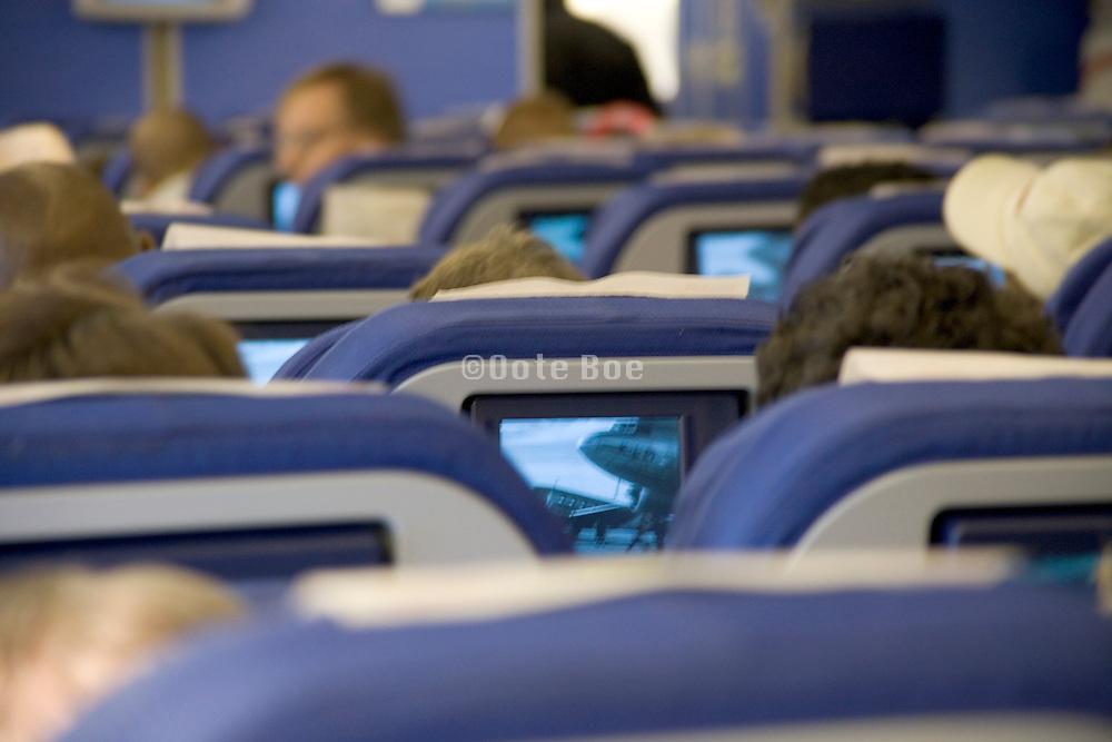 Passengers inside airplane watching mini TV