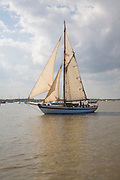Historic wooden sailing yacht boat in full sail at the mouth of River Deben, Suffolk, England
