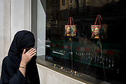 A Muslim lady wearing a Niqab passes the luxury shop window of Louis Vuitton featuring their exclusive range of bags with the face of Leonardo da Vincis Mona Lisa - a collaboration with the artist Jeff Koons and part of work entitled The Masters Collection, on 5th July 2017, on New Bond Street, in London England.