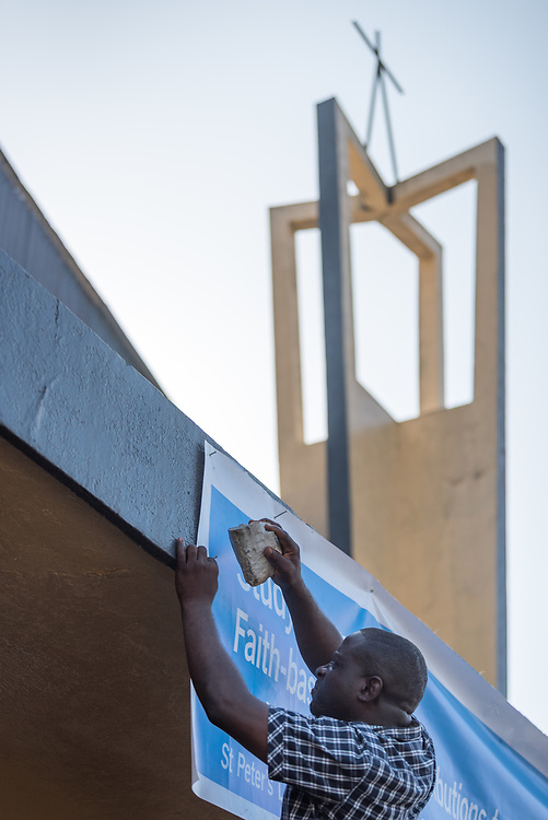 30 October 2019, Monrovia, Liberia: Liberia Council of Churches staff Winston raises a banner at Saint Peter Lutheran Church in Monrovia, known as the site of the 1990 Monrovia Church Massacre, in which some 600 people were killed, during the First Liberian Civil War.