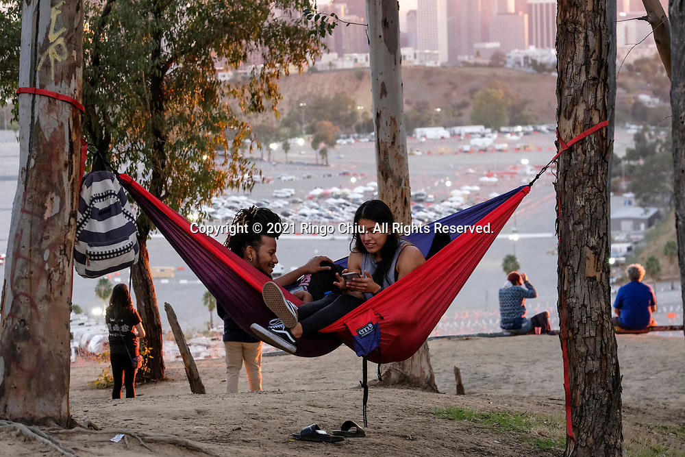 People lay in their hammocks as motorists wait in lines to get the coronavirus (COVID-19) vaccine during the sunset in a parking lot at Dodger Stadium, Friday, Jan. 15, 2021, in Los Angeles. Dodger Stadium reopened Friday as a mass COVID-19 vaccination site, which Mayor Eric Garcetti says will have the capacity to vaccinate 12,000 people a day once it is fully operational.