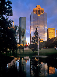 Downtown Houston cityscape featuring the Wells Fargo Plaza on left and Heritage Plaza on right reflected in the pond at Sam Houston Park in late afternoon.