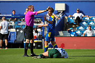AFC Wimbledon midfielder Alex Woodyard (4) talking to ref just before getting a yellow card for foul during the EFL Sky Bet League 1 match between AFC Wimbledon and Plymouth Argyle at the Kiyan Prince Foundation Stadium, London, England on 19 September 2020.