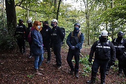 National Eviction Team bailiffs working on behalf of HS2 Ltd form a line in front of an anti-HS2 activist during evictions from a wildlife protection camp in the ancient woodland which inspired Roald Dahl's Fantastic Mr Fox at Jones' Hill Wood on 1 October 2020 in Aylesbury Vale, United Kingdom. Around 40 environmental activists and local residents, some of whom living in makeshift tree houses 60 feet above the ground, were present during the evictions at Jones' Hill Wood which had served as one of several protest camps set up along the route of the £106bn HS2 high-speed rail link in order to resist the controversial infrastructure project.
