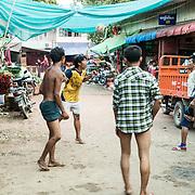 Burmese men playing chinlone (caneball) on a street in Mandalay, Myanmar (Burma).