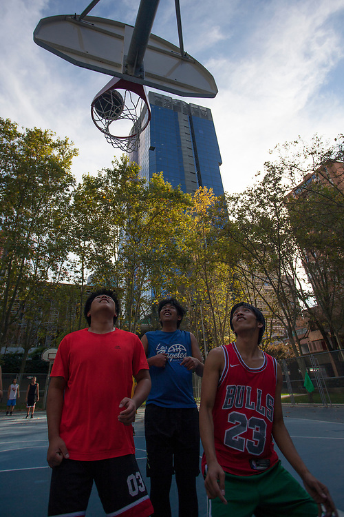 MADRID, SPAIN - OCTOBER 9: Asian young men play basketball on a street court on October 9, 2020 in Madrid, Spain. Azca, considered the business heart of the city, is a business and leisure area in Madrid spanning from Nuevos Ministerios to the Santiago Bernabeu stadium, flanked by Paseo de la Castellana and Calle Orense, two of the most iconic streets in the capital. Madrid's Mayor José Luis Martínez Almeida has announced a partnership with private investors including stock-trading companies Merlin and GMP, in order to revamp the area by promoting the development of a modern space with the best business and leisure facilities. (Photo by Miguel Pereira/Getty Images)