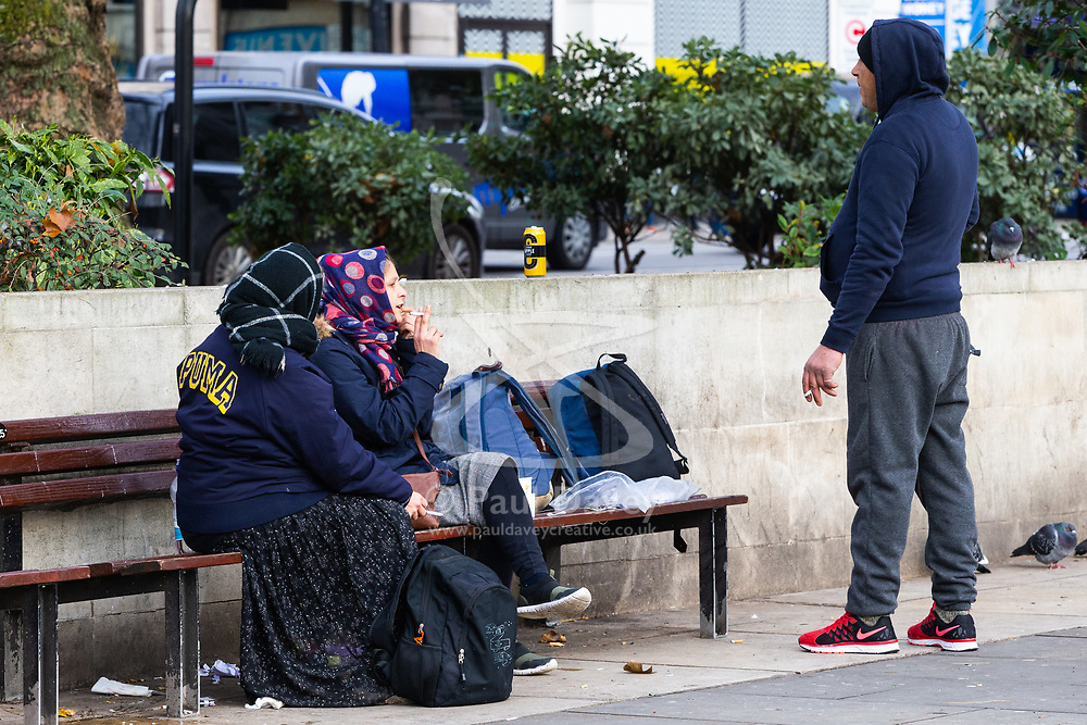 Two women in headscarves and a man appear to have have an animated discussion as they smoke on a bench at Marble Arch. Homeless Britons are coming under increasing pressure as a surge of Roma beggars from Romania arrive on the streets of London to take advantage of the generosity of Christmas shoppers. London, December 04 2018.