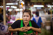 09 OCTOBER 2012 - BANGKOK, THAILAND: A porter waits for a customer in the Bangkok Flower Market. The Bangkok Flower Market (Pak Klong Talad) is the biggest wholesale and retail fresh flower market in Bangkok. It is also one of the largest fresh fruit and produce markets in the city. The market is located in the old part of the city, south of Wat Po (Temple of the Reclining Buddha) and the Grand Palace.    PHOTO BY JACK KURTZ