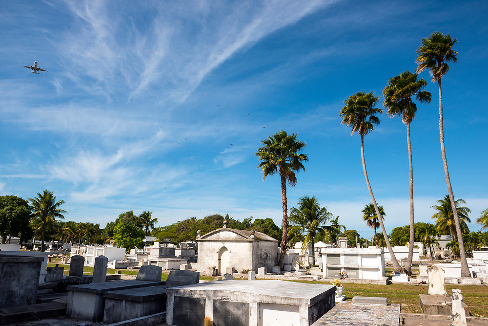 Key West, Florida, USA - January 17, 2015: A plane passes over the historic Key West Cemetery, established in 1847 after a hurricane washed bodies out from their previous location.