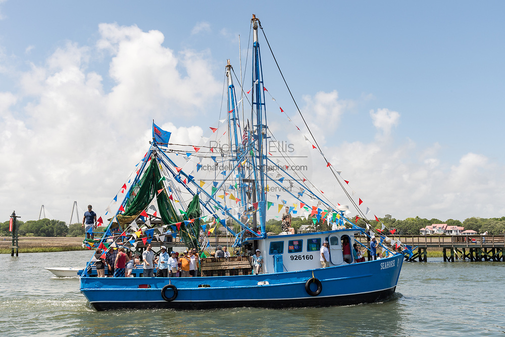 A decorated shrimp boat parades past the commercial fishing docks down Shem Creek during the annual Blessing of the Fleet signifying the start of the commercial shrimping season April 30, 2017 in Mount Pleasant, South Carolina. Coastal shrimping is part of the low country heritage but has been declining rapidly with rising costs and increased foreign competition.