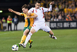 © Licensed to London News Pictures. 11/6/2013. Tom Oar gets tackled by Odai Al Saify  during the FIFA World Cup Qualifying match between Australia Vs Jordan at Docklands stadium, Melbourne, Australia.. Photo credit : Asanka Brendon Ratnayake/LNP