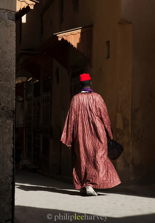 A man wearing a fez walks in the narrow streets of the medina in Fes, Morocco