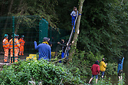 HS2 security guards watch an HS2 Rebellion activist climb a tree in Denham Country Park in order to try to protect it from works for the HS2 high-speed rail link on 8 September 2020 in Denham, United Kingdom. Anti-HS2 activists continue to try to prevent or delay works on the controversial £106bn project for which the construction phase was announced on 4th September from a series of protection camps based along the route of the line between London and Birmingham.