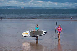 Gullane, Scotland, UK. 9 July, 2020. Signs and one-way system on beach paths have been introduced at beaches in East Lothian. To maintain social distancing some paths are one-way only. Pictured; Women enjoy watersports and maintain social distancing on Gullane Beach.  Iain Masterton/Alamy Live News