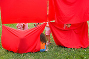 Kids playing in red banners at a summer music & art event.