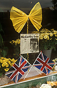 Seen in a local shop window, is a newspaper cutting, yellow ribbon and Union Jack flags mark the release of Beirut hostage, the TV journalist John McCarthy. The headline says 'McCarthy Free' in a simple, long-awaited announcement. John Patrick McCarthy CBE (born 27 November 1956) is a British journalist, writer and broadcaster, and one of the hostages in the Lebanon hostage crisis. He was kidnapped by Islamic Jihad terrorists in Lebanon in April 1986, and held hostage for more than five years. He was appointed a Commander of the Order of the British Empire in 1992. McCarthy was Britain's longest-held hostage in Lebanon, having spent over five years in captivity until his release on August 8, 1991. He shared a cell with the Irish hostage Brian Keenan, for several years.