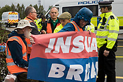 Metropolitan Police officers monitor Insulate Britain climate activists who had previously blocked a M25 slip road at Junction 14 close to Heathrow airport as part of a campaign intended to push the UK government to make significant legislative change to start lowering emissions on 27th September 2021 in Colnbrook, United Kingdom. The activists are demanding that the government immediately promises both to fully fund and ensure the insulation of all social housing in Britain by 2025 and to produce within four months a legally binding national plan to fully fund and ensure the full low-energy and low-carbon whole-house retrofit, with no externalised costs, of all homes in Britain by 2030.