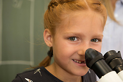 Close-up of a School girl smiling with microscope, Fürstenfeldbruck, Bavaria, Germany