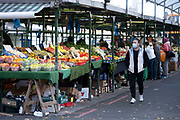 With a fraction of the normal numbers of shoppers around on the day that the second national lockdown came into effect, some people, many of whom are wearing face masks, come to a very quiet open fruit and veg market in the city centre as all non-essential shops are closed while others remain trading on 5th November 2020 in Birmingham, United Kingdom. The new national lockdown is a huge blow to the economy and for individual businesses who were already struggling with only offering limited services.