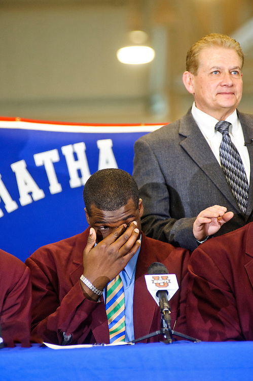 """When asked where he will attend over the ESPNU televised signing day event the DeMatha Catholic School's offensive tackle Cyrus Kouandjio, said """"Auburn."""" However, Kouandjio, one of the nation's top high school football players, never signed his letter of intent during his school's signing day event February 2nd, 2011. Three days later he announced he will attend Alabama where his older brother plays. Head football coach and the school's athletic director Bill McGregor stands behind the table of his players."""