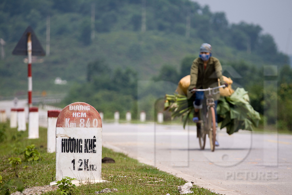 Woman riding a bicycle along Ho Chi Minh highway, Ha Tinh Province, Vietnam, Southeast Asia