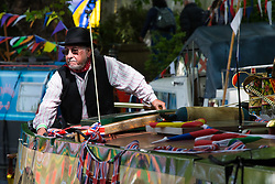 Little Venice, London, April 30th 2017. Narrowboaters from all over the uK gather for the annual Canalway Cavalcade, held on the May Day Bank holiday weekend, organised by the Inland Waterways Association, where boaters get the chance to display their immaculately prepared and brightly painted craft as well as compete in various manoeuvring tests. PICTURED: A narrow boater in traditional dress manoeuvres his craft through the canal.<br /> Credit: ©Paul Davey<br /> To licence contact: <br /> Mobile: +44 (0) 7966 016 296<br /> Email: paul@pauldaveycreative.co.uk<br /> Twitter: @pauldaveycreate