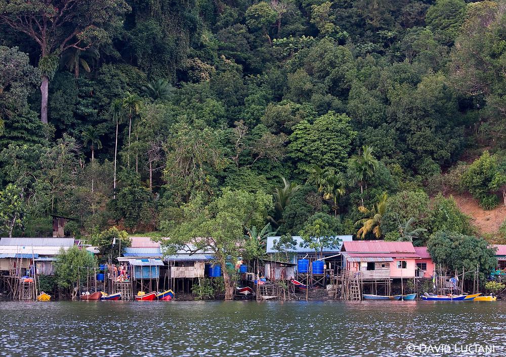 Houses on stilts, lined up along the Santubong riverbank.