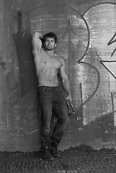shirtless man by a graffiti wall