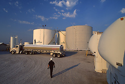 Stock photo of a man walking to his truck parked beside large storage tanks
