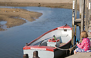 Little girl with a crabbing line and boats on the quayside at Blakeney, Norfolk, England