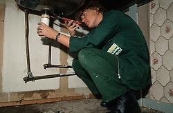 Plumber at work mending sink,