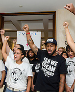Melanie Andrade, president of the Florida A&M chapter of Dream Defenders, and Phillip Agnew, director of Dream Defenders, raise their fists in solidarity with other group members following a press conference July 23, 2013 in the Florida state capitol in Tallahassee. The youth-led activist group is pressuring Florida Gov. Rick Scott to call a special legislative session to address issues like racial profiling, the school-to-prison pipeline, and Florida's stand-your-ground law. (Photo by Carmen K. Sisson/Cloudybright)