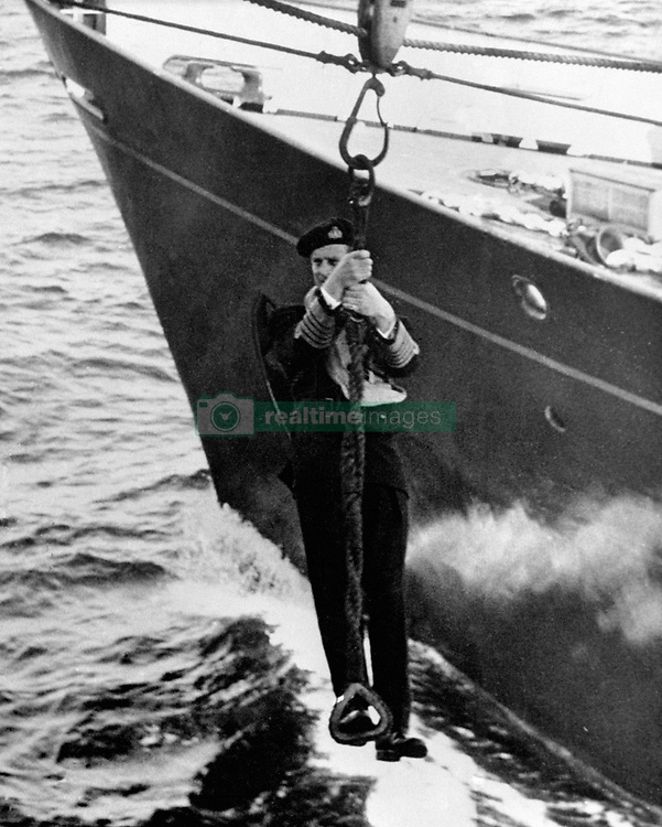 File photo dated 01/04/55 of The Duke of Edinburgh transferring ships by jackstay, during the Home Fleet's passage home from Malta after the combined naval exercises in the Mediterranean. Philip joined the Navy after leaving school and in May 1939 enrolled at the Royal Naval College in Dartmouth, where he was singled out as best cadet. He rose rapidly through the ranks, earning promotion after promotion, but his life was to take a very different course. The duke's flourishing naval career came to a premature end in 1951. Philip stepped down from his active role in the forces to fulfil his duty as consort. Issue date: Friday April 4, 2021.