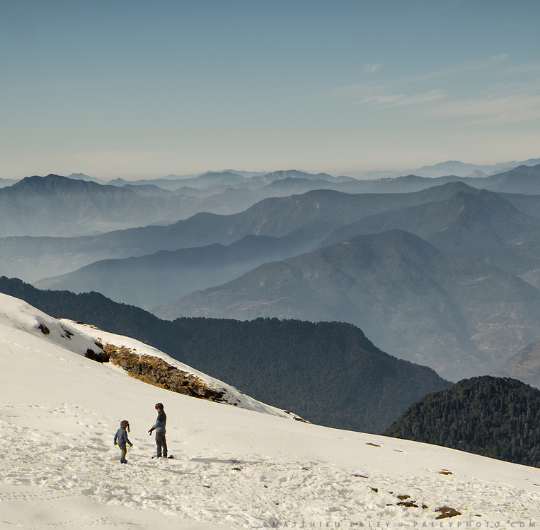Two young brothers plays in snow in front of a vast mountain landscape.