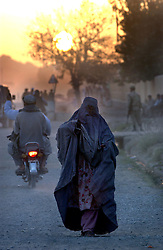 KANDAHAR,AFGHANISTAN - SEPT.6 : An Afghan woman walks next to the Governor's house September 6, 2002 in Kandahar, Afghanistan. The city remains tense after Kandahar Governor Gul Agha Sherzai was shot during an apparent assassination attempt on President Hamid Karzai yesterday evening. .(Photo by Ami Vitale/Getty Images)