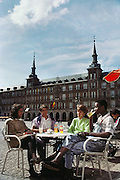 Young people at a café in the Plaza Mayor, Madrid, Spain.
