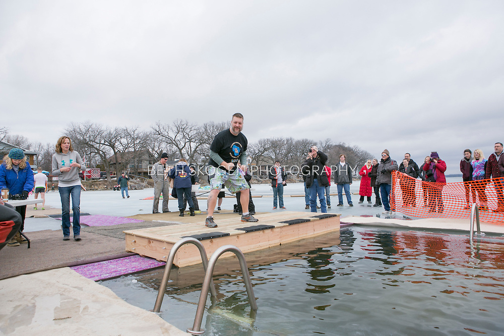 Shadow Drum and Bugle Corps members jump into a frozen lake for the Wisconsin Winter Plunge to raise funds for the organization in Madison, Wisconsin on February 21, 2016. <br /> <br /> Beth Skogen Photography - www.bethskogen.com