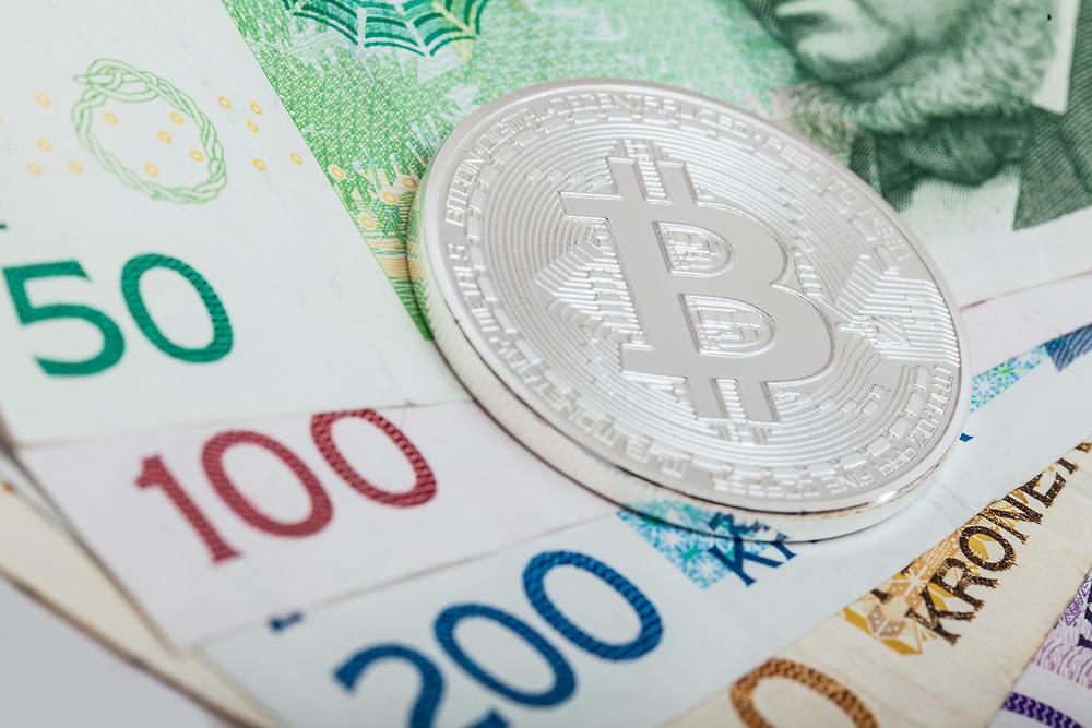 En bitcoin-mynt som ligger på norske sedler. Foto egnet til å illustrere det meste som vedrører kryptovaluta kontra regulert økonomi.