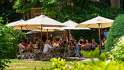 Busy cafe in garden at Literaturhaus cultural centre in Berlin, Germany