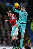Goalkeeper Thibaut Courtois of Chelsea leaps to save over Wayne Rooney, the Manchester United captain . Barclays Premier league match, Chelsea v Manchester Utd at Stamford Bridge in London on Sunday 7th February 2016.<br /> pic by John Patrick Fletcher, Andrew Orchard sports photography.