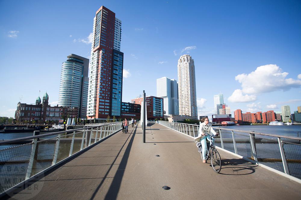 In Rotterdam steken fietsers en voetgangers de Rijnhavenbrug over tussen de wijkdelen Rotterdam Zuid en Katendrecht. De brug wordt in de volksmond 'hoerenloper' genoemd, omdat voorheen Katendrecht een prostitutiegebied was. In de achtergrond Hotel New York (laag gebouw links), Montevideo, Las Palmas (het lage witte gebouw met oa het Nederlands fotomuseum), De Rotterdam (blauwgrijs gebouw) van OMA/Rem Koolhaas) en de New Orleans.<br /> <br /> In Rotterdam cyclists and pedestrians are passing the bridge between the districts Rotterdam Zuid and Katendrecht.  In the background Hotel New York (low building left), Montevideo, Las Palmas (low white building), De Rotterdam (blue grey building) by OMA/Rem Koolhaas) and the New Orleans.