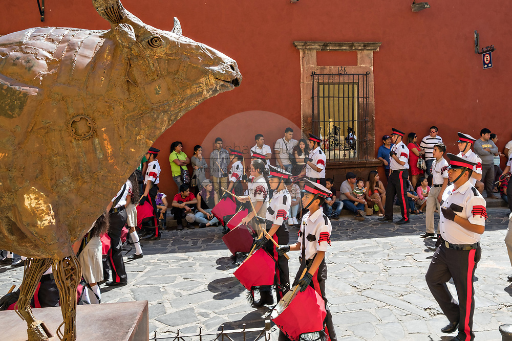 A military school band parades through the historic district past a sculpture of a bull during Mexican Independence Day celebrations September 16, 2017 in San Miguel de Allende, Mexico.