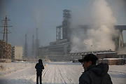 Two men wait for a bus to arrive on a snow covered street as water vapor and smoke rise from a Tonghua Iron & Steel Group Co. plant in the distance in the Erdaojiang district in Tonghua, Jilin province, China, on Wednesday, Jan. 6, 2016. The citys once-vaunted state-run steel mills have slipped inexorably into decline, weighed down by slumping global markets, a changing economy, and the burden of costs and responsibilities to the people of the town they fostered. Previous attempts to privatise the enterprise have met with stiff resistance, one such attempt resulted the mob lynching and death of a private businessman who wanted to invest and streamline the operation.