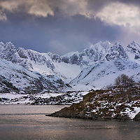 The magical arctic light falls upon the snow capped peaks in the Lofoten Islands of northern Norway.