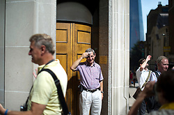 © London News Pictures. 04/09/2013. London, UK. A man wipes sweat from his forehead as he stands in the suns light reflecting off 20 Finchurch Street in the financial district of central London. The building, which has been named unofficially the 'Walkie Talkie' building because of its shape, intensifies the suns light and reflects it onto the street below. There have been reports of damage to vehicles and local shops caused by the heat of the reflected light. Photo credit: Ben Cawthra/LNP