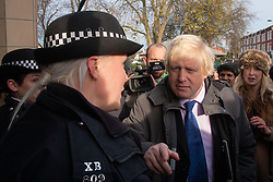 Ealing, London, December 9th 2014. Mayor of London Boris Johnson visits Ealing accompanied by Met Police Commissioner Sir Bernard Hogan-Howe hold a walkabout in Ealing to announce details of the historic deal secured for the New Scotland Yard site in Victoria. PICTURED: Boris Johnson talks with a police officer outside Ealing Broadway station.