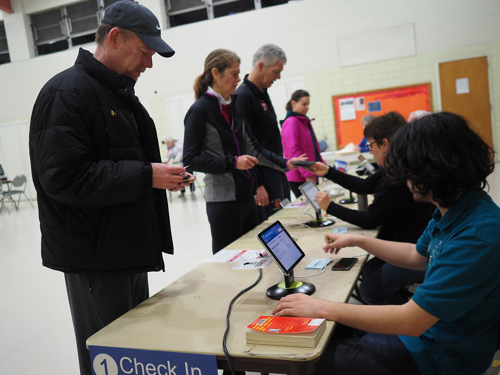 Early morning Virginia voters present ID as they check in to vote on Presidential Primary Day.