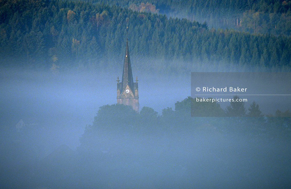 Seen from across a hillside opposite, we see the rising and imposing steeple of the L'église de l'Assomption de Notre-Dame church (1717 ) in Ban-de-Laveline in the Vosges mountain of eastern France. Through fast-clearing mist, the spire is a beautiful early morning sight amongst the evergreen forests on the far hills.